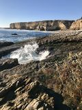 California coastline including cliff, rocky shore, beach, ocean with gentle waves, and clear blue sky. Landscape of California coastline including cliff, rocky stock image