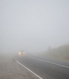Landscape with a car on the road in the fog with headlights incl Stock Photography