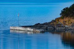 Loneliness on the dock by the lake. Landscape of cement quay in Puerto Guadal on the shores of Lake General Carrera in the Patagonia of Chile in the Region of stock photos