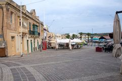 Malta, Marsaxlokk: Central square of fishermen village. Landscape of the central village square in Marsaxlokk, Malta. There are painted wooden balconies and royalty free stock photos