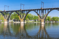 Landscape with classic arched bridge and it`s reflection on the Dnipro river the water in the Dnipro city, Ukraine. Spring landscape with classic arched bridge Royalty Free Stock Photography