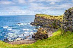 Landscape of cliffs at Dunluce Castle on Antrim coast, Northern Ireland. Beautiful scenery on Northern Ireland rugged coastline Royalty Free Stock Images