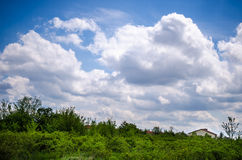 Landscape with clouds on blue sky. Village, landscape in a summer day with blue sky and clouds Royalty Free Stock Photo