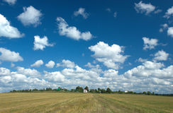 Landscape with clouds over field Royalty Free Stock Images
