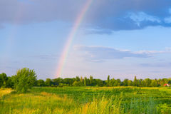 Landscape with clouds and rainbow. Green grass field with rainbow in the background Royalty Free Stock Image