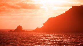 Landscape with coastal rocks in red sunlight Stock Photography