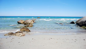 Landscape with coastal sea shore, waves, crystal clear water. And rocks and clear sky as wounderful image stock photos
