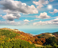 Landscape of colorful autumn forest by the sea on cloudy sky Stock Image