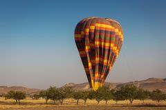 Landscape with colorful hot air balloon deflating over a beatiful blue sky in background.  royalty free stock image
