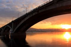 Landscape with Communal Bridge over the Yenisei river. Winter golden sunset over the Yenisei river in Krasnoyarsk. The sun is reflected in the mirror-like Stock Photos