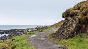 Landscape composition of a windy path beside the coast. Lonely coastal dirt track near Dunvegan castle in Skye in the highlands of Scotland. The windy path goes Royalty Free Stock Image