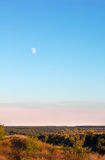 Landscape consisting of the moon, the sky, a valley and trees Stock Image