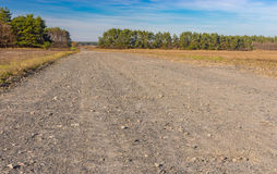 Landscape with country macadam road leading to remote Ukrainian village Hetmanka in Poltavsk region. Fall landscape with country macadam road leading to remote Royalty Free Stock Photos