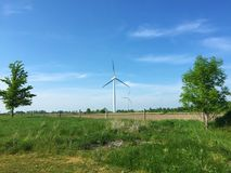 Landscape of the country side featuring a wind turbine on a bright summer day generating electricity. Landscape of the country side featuring a wind turbine on a Royalty Free Stock Images
