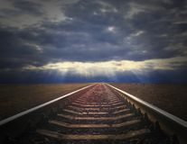 The landscape with dark evening clouds and rails going away Stock Image