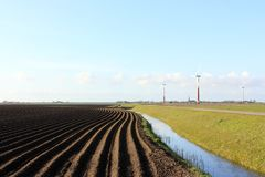 Landscape with dark plowed field and wind turbines stock image