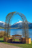 Landscape with decorative arch. Decorative arch and a bench by a mountain lake. Schliersee lake near Tegernsee, German Alps, Bavaria, Germany Stock Photography
