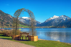 Landscape with decorative arch. Decorative arch and a bench by a mountain lake. Schliersee lake near Tegernsee, German Alps, Bavaria, Germany Royalty Free Stock Photo