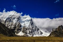Landscape of deep blue sky and ice capped peaks of himalayan mountains with white clouds during day time.  Stock Photos