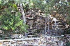 Landscape design. Decorative stone waterfall pond near swimming pool in the park zone. landscape design. close up.green shrubs Stock Photo