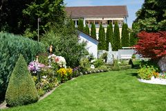 Landscape design of garden with grass and flowers Stock Photos