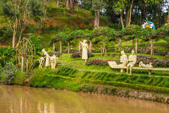 Landscape design of relax tropical garden with statues on a river side Royalty Free Stock Images