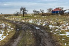 Landscape with an dirty earth road leading to remote Ukrainian village in Sumskaya oblast. Rural landscape with an dirty earth road leading to remote Ukrainian Royalty Free Stock Images