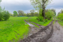Landscape with dirty road in rural Ukrainian area at spring season Stock Photo