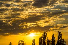 Landscape with dramatic light - beautiful golden sunset with saturated sky and clouds. Peaceful nature serene background royalty free stock photography