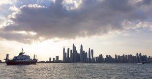 Landscape of Dubai city skyline at sunset with clouds and ship. Landscape of the Dubai city skyline at sunset with clouds and ship royalty free stock photo
