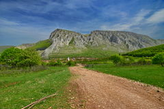 Landscape with dusty road to Rimetea village and Piatra Secuiului. Royalty Free Stock Image