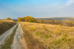 Landscape with earth road leading to remote village Grusheve in Sumskaya oblast, Ukraine Royalty Free Stock Photos