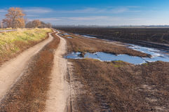 Landscape with earth road near agricultural field. Autumnal landscape with earth road near agricultural field Stock Images