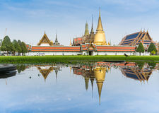 Landscape of Emerald Buddha temple and water reflection on grass field Royalty Free Stock Photography