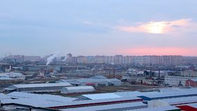 Landscape of evening city with high-rise buildings under construction, factories and pipes of which there is smoke stock footage