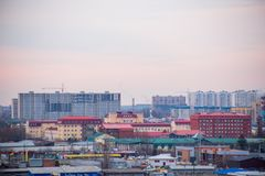 Landscape of evening city with high-rise buildings under construction, factories and pipes of which there is smoke royalty free stock images