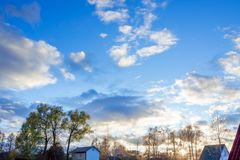 Landscape evening twilight and autumn sunset. Trees and roof houses on background blue sky with white clouds. landscape evening twilight and autumn sunset Royalty Free Stock Photo