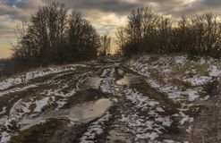 Landscape with extremely dirty road leading to small Ukrainian village Shpilivka in Sumskaya oblast, Ukraine Stock Image
