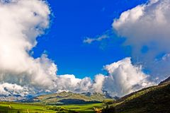 Landscape of farmland, mountains and clouds. Landscape with fruit plantations in a valley, mountains and clouds on mountain plateau above Piketberg, South Africa royalty free stock image