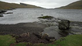 Landscape of Faroe Islands. Beautiful landscape of a river with rocky shores on the background of the faded cliffs and the cloudy sky on Faroe Islands. Strong stock footage