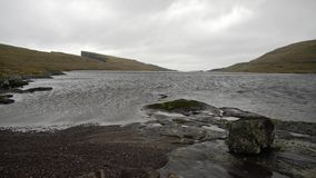 Landscape of Faroe Islands. Dramatic landscape of a river with rocky shores on the background of the faded cliffs and the cloudy sky on Faroe Islands. Strong stock footage