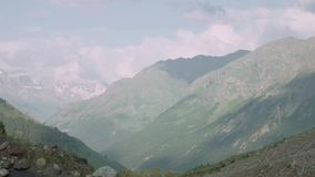 Landscape of stony stream in mountain covered in green trees, snowy peaks. Landscape of fast stony stream in mountain covered in green trees, snowy peaks. Sunny stock video footage