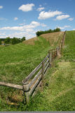 Landscape - Fence, Grass, Blue Sky and Clouds. A tranquil view of the fence line running along the edge of a central Virginia farm, with rolling hills, bright Royalty Free Stock Photos
