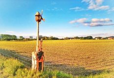 Landscape with field and abandoned rail crossing. An old railway level crossing and countryside landscape stock image