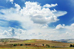 Landscape with field, blue sky, clouds and wind energy generators turbine Stock Images