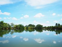 Landscape of fishing pond on sunny day with reflection. Of blue sky and green tree in the water royalty free stock photos
