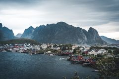 Landscape of fishing village Reine with the Reine Fjord during sunset with nice lights on mountain, blue sky and clouds. Lofoten, Norway. Photo taken in Norway royalty free stock images