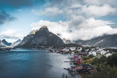 Landscape of fishing village Reine with the Reine Fjord during sunset with nice lights on mountain, blue sky and clouds. Lofoten, Norway. Photo taken in Norway stock images
