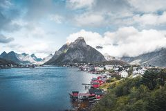 Landscape of fishing village Reine with the Reine Fjord during sunset with nice lights on mountain, blue sky and clouds. Lofoten, Norway. Photo taken in Norway royalty free stock photography
