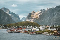 Landscape of fishing village Reine with the Reine Fjord during sunset with nice lights on mountain, blue sky and clouds. Lofoten, Norway. Photo taken in Norway royalty free stock photos